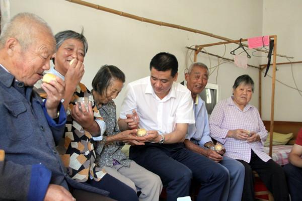 2012年9月,甘金华到新洲汪集第二福利院看望老人,并送去月饼等慰问品.jpg