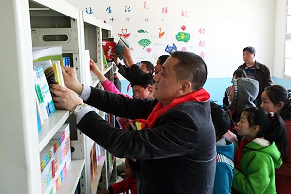 甘金华加入省慈善总会慈善书屋捐赠仪式,和孩子们一起整理书籍.jpg