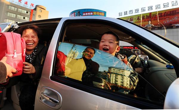 """2014年元月,甘金华捐款10万元为留守儿童购票圆梦,并与 """"慈善圈""""好友奔赴仙桃接留守儿童去父母身边过年。.JPG"""