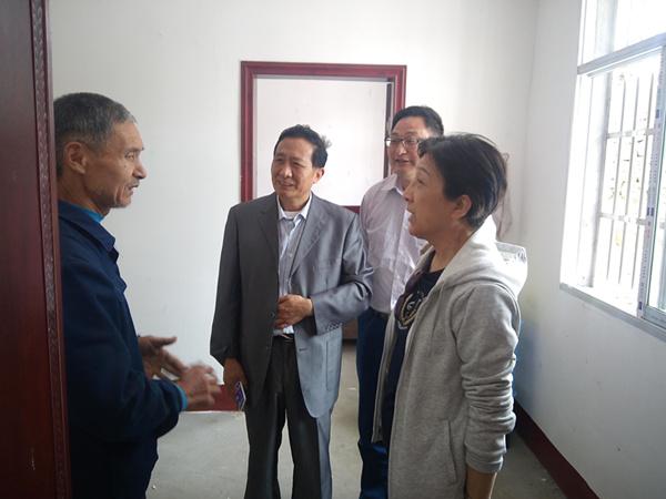 """贾虹副会长(右一)向乌石山村因灾倒房""""五保老人""""了解入住情况.png"""